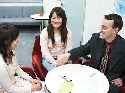 英会話スクールトーク・アベニューのレッスン風景の写真。ネイティブ講師1名に生徒2名でのレッスンの様子