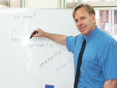 英会話スクールトーク・アベニューの授業風景。ホワイトボードを背に授業をしているネイティブ講師